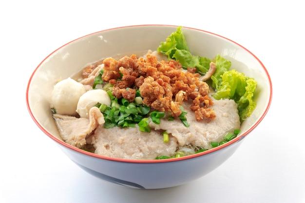 Macarrão tailandês com máquina de porco e bola de carne e legumes frescos e sopa quente