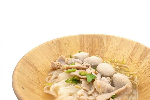 Macarrão tailandês e almôndega na tigela de bambu isolar no fundo branco