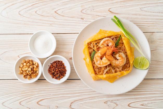 Macarrão tailandês frito com camarão e embrulho de ovo (pad thai) - estilo de comida tailandesa