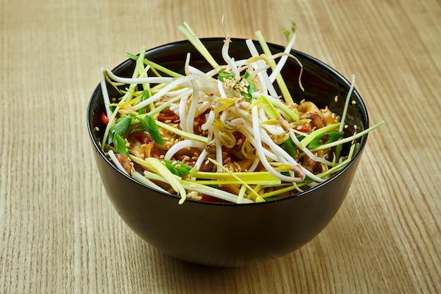 Macarrão tailandês tradicional com carne de porco ou frango em molho agridoce, cebola em uma tigela preta sobre uma superfície de madeira