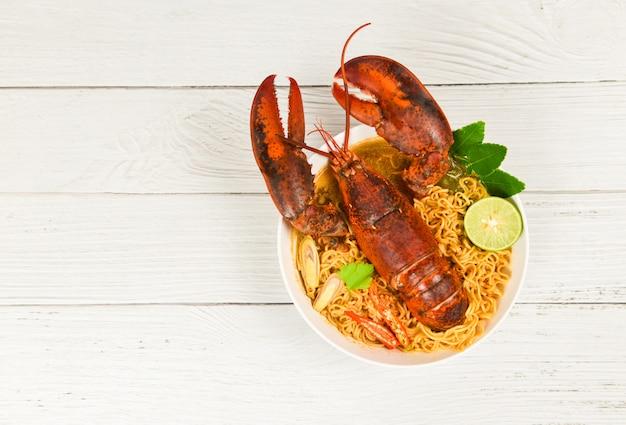 Macarrão tigela lagosta sopa picante / frutos do mar cozidos com macarrão instantâneo sopa de lagosta mesa de jantar e temperos ingredientes na mesa comida tailandesa