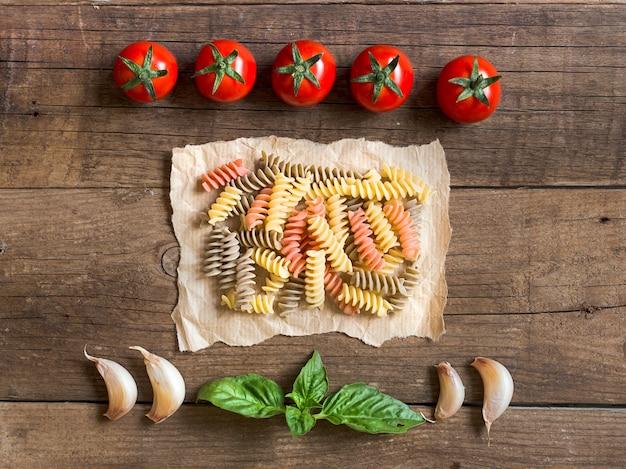 Macarrão, tomate, alho e manjericão na vista superior do plano de fundo de madeira