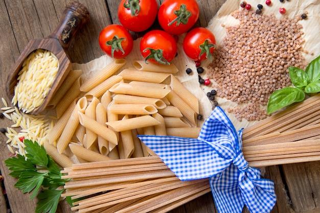 Macarrão, tomate e manjericão na vista superior do plano de fundo de madeira