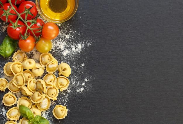 Macarrão tortellini fresco e ingredientes em um quadro escuro com vista de cima
