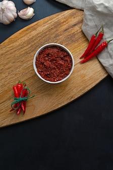 Macarrão tradicional com molho de pimenta quente maghreb, harissa em uma mesa de ardósia escura, cozinha tunisina, árabe, culinária mexicana, adjika, muhammara. orientação vertical com lugar para texto