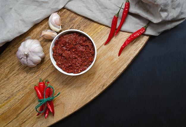 Macarrão tradicional com molho de pimenta quente maghreb, harissa sobre um fundo escuro de ardósia, cozinha tunisina, árabe, cozinha mexicana, adjika, muhammara. orientação horizontal com lugar para texto