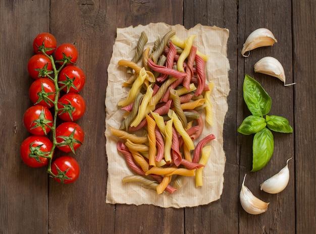 Macarrão tricolor com tomate cereja, alho e manjericão na mesa de madeira