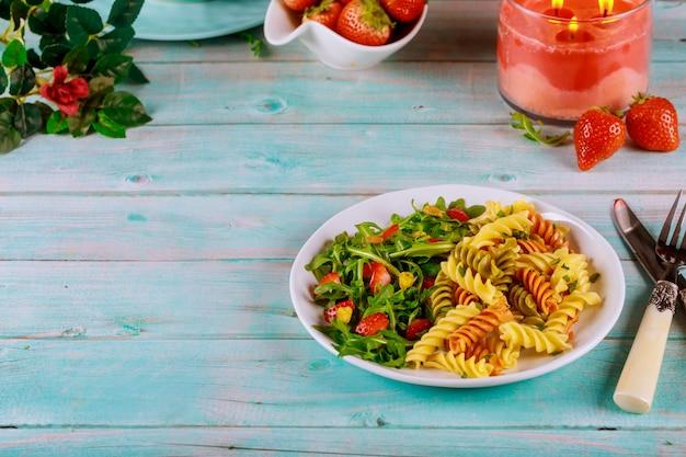 Macarrão tricolor rotini de trigo duro com salada verde na mesa de madeira