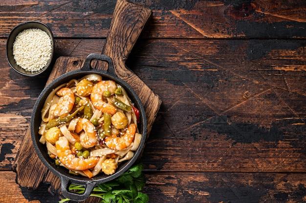 Macarrão udon asiático frito com camarões camarões em uma panela. madeira escura