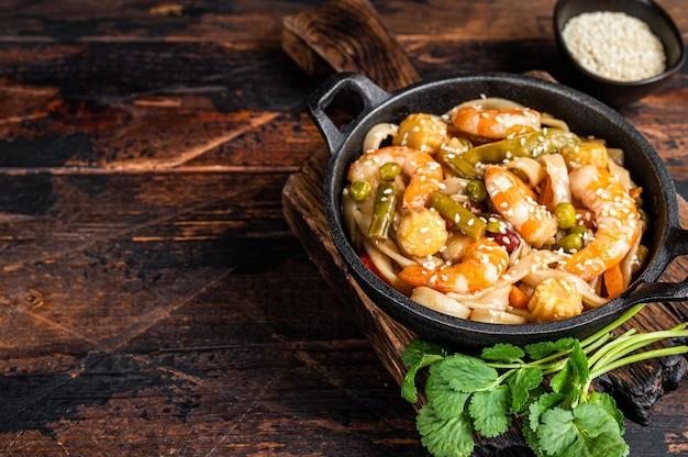 Macarrão udon asiático frito com camarões camarões em uma panela.