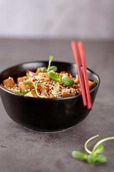 Macarrão vegetariano com queijo tofu e legumes em uma placa de cerâmica preta.