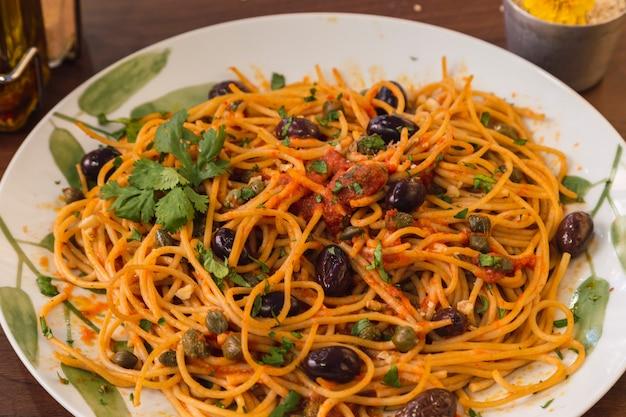 Macarrão vegetariano italiano de close-up com molho de tomate, azeitonas, manjericão fresco, alcaparras e orégano.