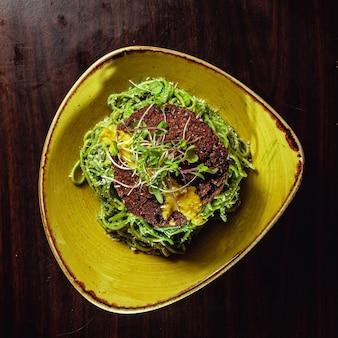 Macarrão verde com um pedaço de pão dietético por cima