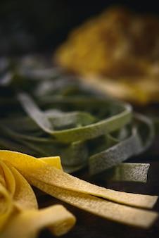 Macarrão verde e amarelo na mesa da cozinha