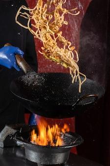Macarrão voador para wok box com carne, molho de soja frito em uma frigideira wok, comida de rua.