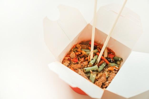 Macarrão wok em caixa para viagem. macarrão de trigo com pato laqueado e legumes. cozinha tradicional chinesa.