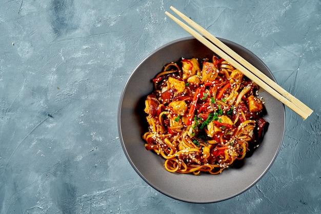 Macarrão wok - udon com frango agridoce e vegetais em um prato cinza sobre um fundo cinza