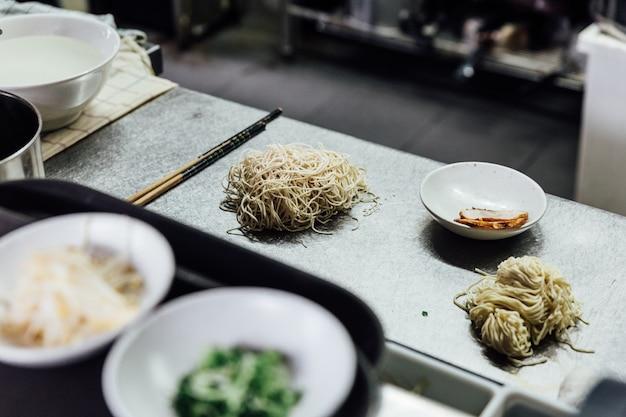 Macarronete de ramen cru do estilo de hakata com carne de porco do chashu no contador de cozinha.