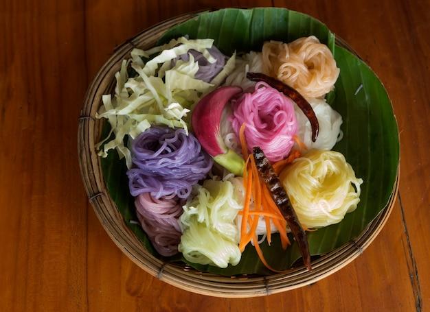 Macarronete tailandês colorido com pimentão, cenoura, couve cortada na folha da banana na cesta.