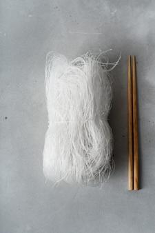 Macarronetes de arroz finos crus com as varas na superfície de pedra. lay plana