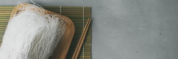 Macarronetes de arroz finos crus na placa de bambu na superfície da pedra com varas. banner longo e largo.