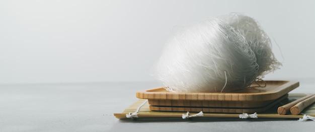 Macarronetes de arroz finos crus no prato de bambu na superfície da pedra com hashis. banner longo e largo.