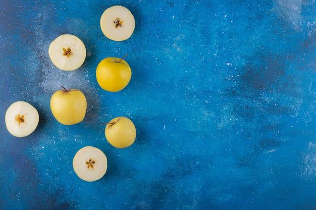 Maçãs amarelas frescas inteiras e fatiadas na superfície azul.
