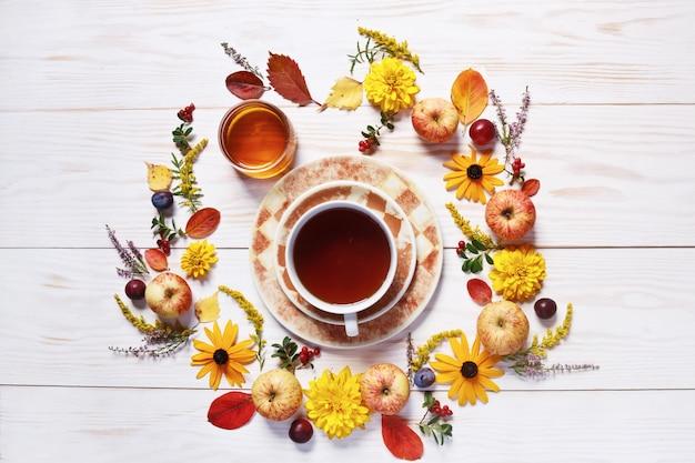 Maçãs, ameixas, mel fresco, xícara de chá, frutas vermelhas e lindas flores