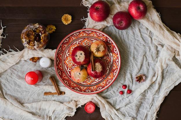 Maçãs assadas com queijo cottage em um prato vermelho com um padrão uzbeque na madeira