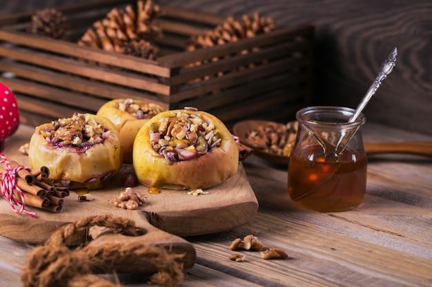 Maçãs assadas recheadas com frutas, nozes e mel em uma tábua de madeira.