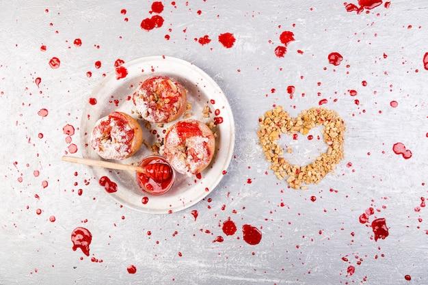 Maçãs assadas vermelhas recheadas com requeijão e granola com geléia. comida de dieta saudável. coração de granola.