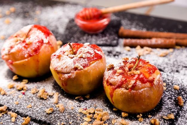 Maçãs assadas vermelhas recheadas com requeijão e granola com geléia. comida de dieta saudável.