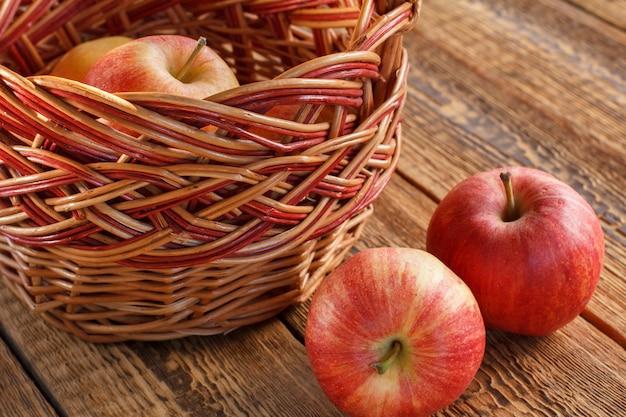 Maçãs colhidas em uma cesta de vime em velhas tábuas de madeira. apenas frutas colhidas.