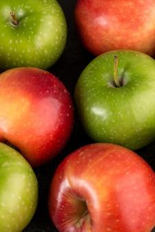 Maçãs coloridas frescas maduras maduras perfeitas isoladas no chão escuro