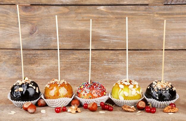 Maçãs de caramelo doce em palitos com bagas, na mesa de madeira