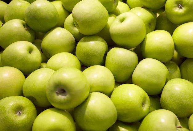 Maçãs de cor verde, muitos pedaços, maduras, amontoadas a granel