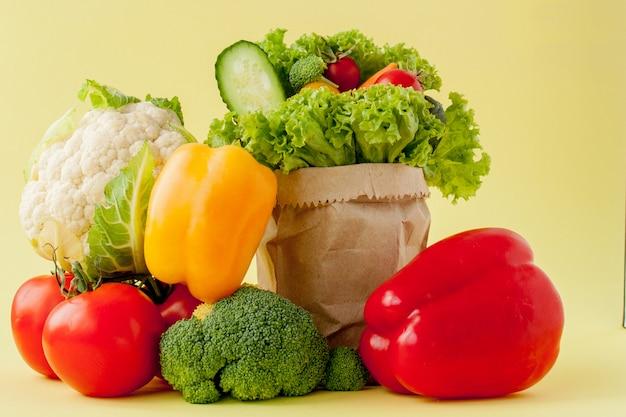 Maçãs de pimentão de pepinos de brócolis de legumes orgânicos em sacola de papel kraft. vegan de fibra dietética de dieta saudável