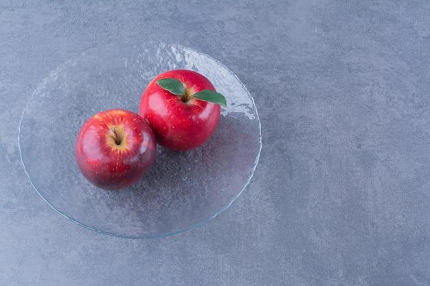 Maçãs deliciosas em uma placa de vidro na mesa de mármore.