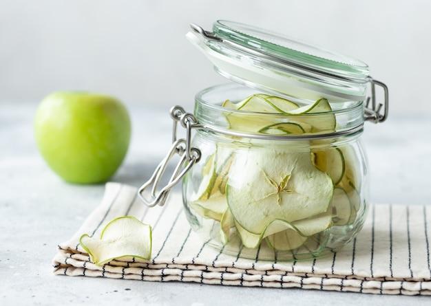 Maçãs desidratadas em frasco de vidro. lanche de frutas veganas