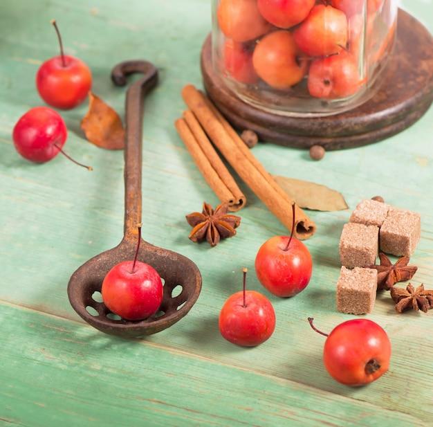 Maçãs do paraíso, na mesa de madeira no estilo rústico, caneca de ferro.
