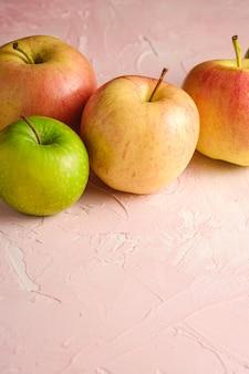 Maçãs doces frescas na parede texturizada rosa, espaço de cópia de vista de ângulo