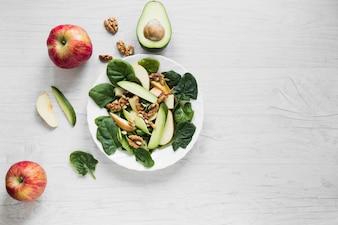 Maçãs e abacate perto de salada