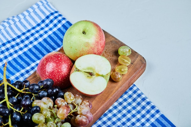 Maçãs e cacho de uvas na placa de madeira com toalha de mesa.