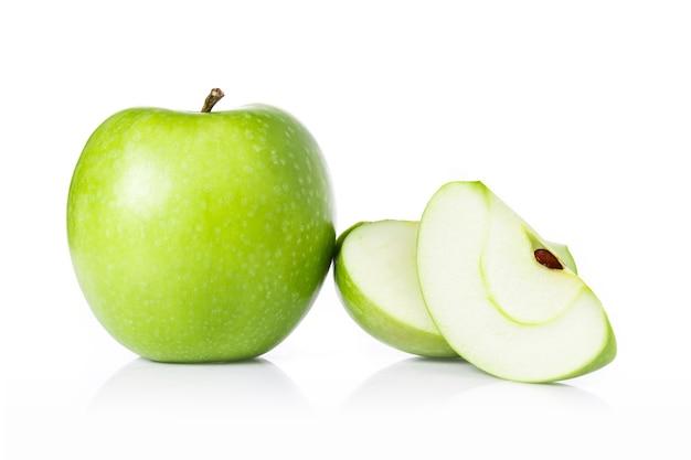 Maçãs e fatias verdes da maçã isoladas no branco.