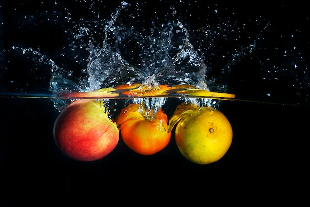 Maçãs e laranja espirrando em respingos de água azul claro