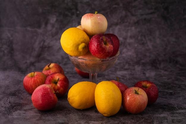 Maçãs e limões de frutas frescas em um vaso de vidro sobre uma mesa de mármore.