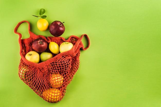 Maçãs e limões em um saco de cordas laranja sobre fundo verde