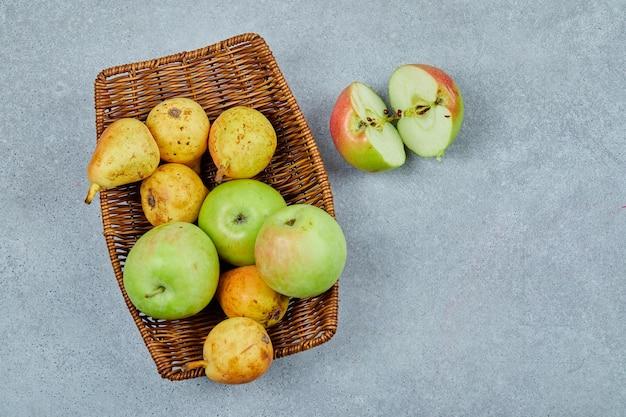 Maçãs e peras na cesta em cinza.