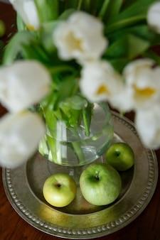 Maçãs e tulipas verdes em uma bandeja de metal redonda em uma mesa de madeira marrom
