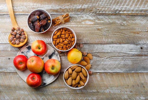 Maçãs em um prato com paus de canela, tâmaras, amêndoas descascadas e com casca em tigelas, nozes na vista superior da colher de pau, sobre um fundo de madeira